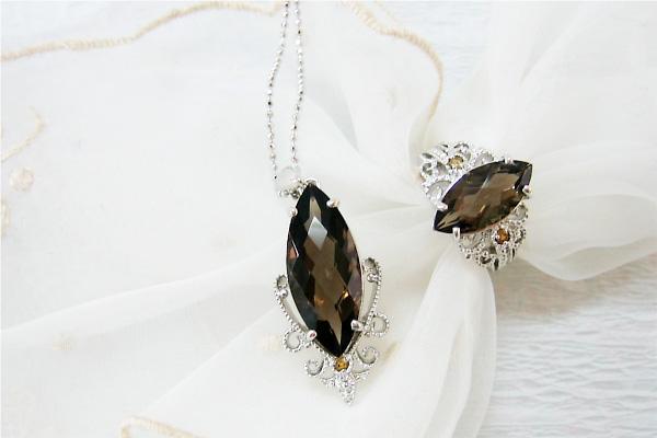 レリーフ調のデザインと宝石をあしらったペンダントヘッドとリング